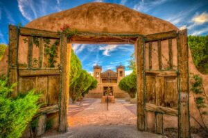 A view through the arched gateway at El Santuario de Chimayó. This Spanish Colonial-style church was built in 1816 and is considered the most popular Catholic pilgrimage shrine in the U.S. The santuario is located in Chimayo, New Mexico. This mission is located along the High Road to Taos.