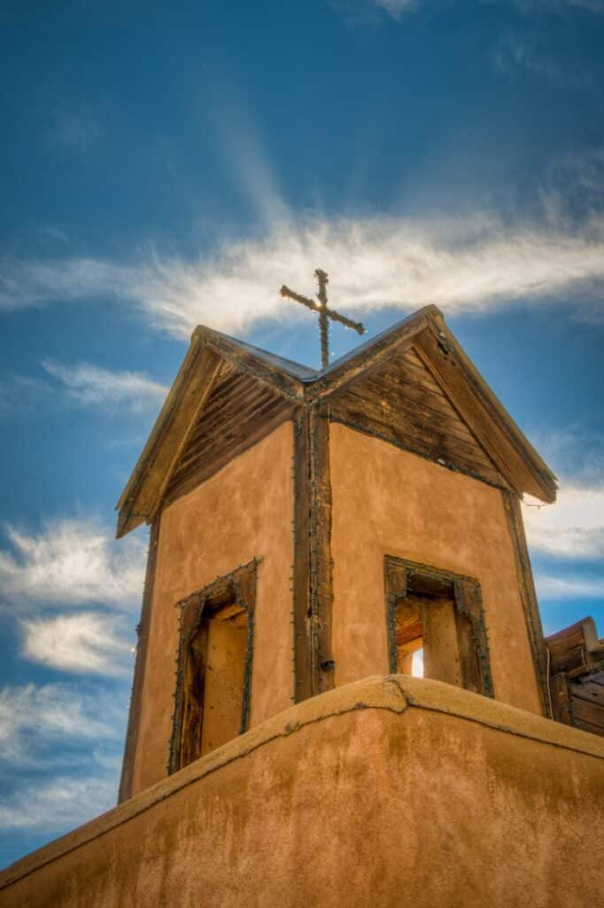 A view looking up at one of Santuario de Chimayo's bell towers with a cross at the tope. The cross is wrapped in mini Christmas lights. The santuario is located in Chimayo, New Mexico.