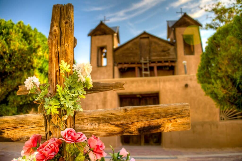 A close-up of a decorated wooden cross in the forecourt of El Santuario de Chimayo, Chimayo, New Mexico.