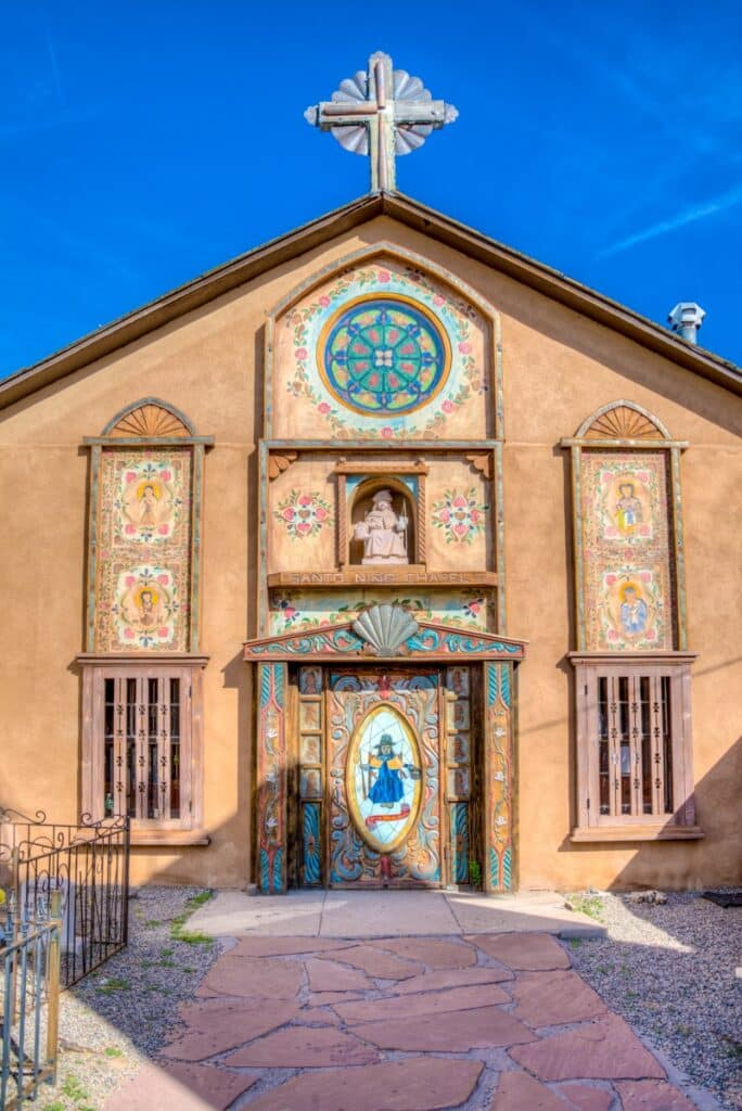 This is a view of the front of Santo Nino Chapel, located in the El Santuario de Chimayo complex in Chimayo, New Mexico. It was built in 1856 and was renovated in 1992 to be a children's chapel.