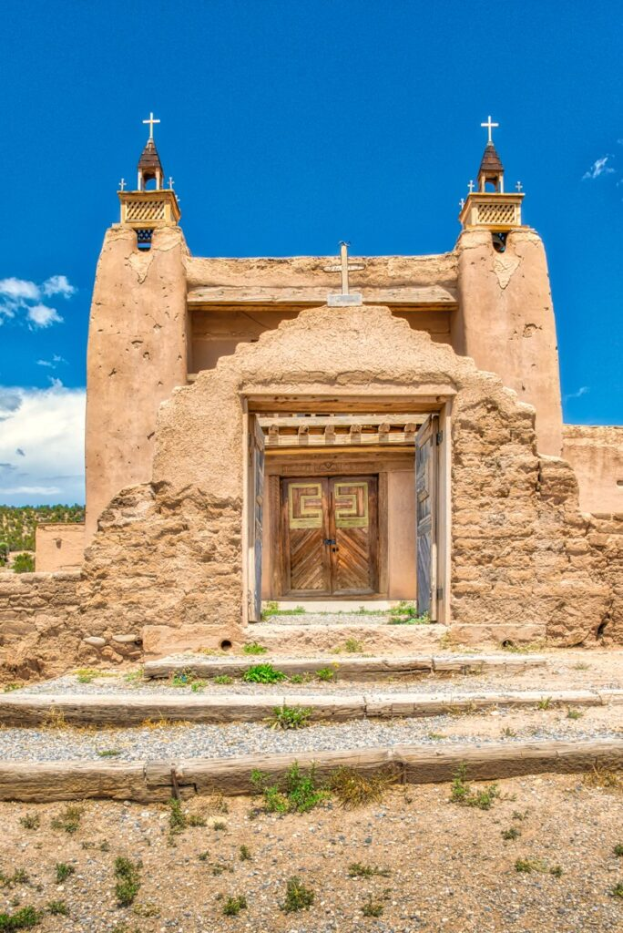 A view through the arched gateway toward the double wooden doors of the San Jose de Gracia church. The San Jose de Gracia Church, also known as Church of Santo Tomas Del Rio de Las Trampas, is a historic church on the main plaza of Las Trampas, New Mexico.