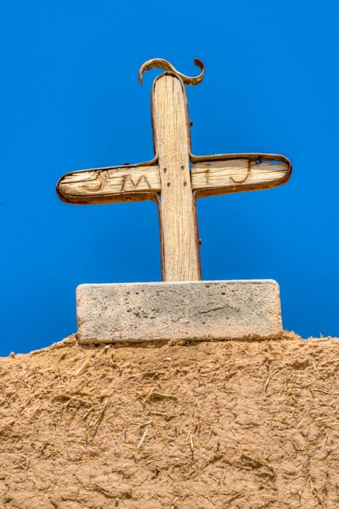 This is a close-up of the cross that is atop the archway of the gate to the church. The San Jose de Gracia Church, also known as Church of Santo Tomas Del Rio de Las Trampas, is a historic church on the main plaza of Las Trampas, New Mexico.