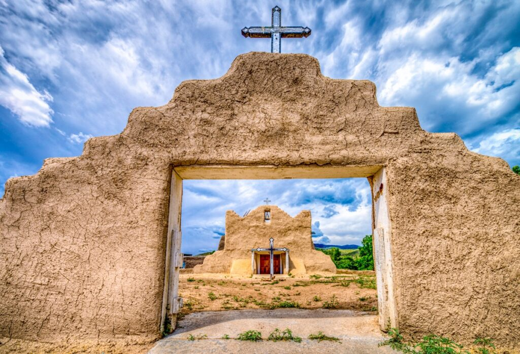 "The San Lorenzo de Picuris Mission Church, located in Picuris Pueblo near Peñasco, NM, was orinially built in 1621. The building we see today is in a slightly different location within the pueblo. construction was started around 1776 and was visited by Father Visitor Domínguez. The church was ""modernized"" in the early 20th Centuray with a pitched metal roof and other so-called improvements. In the 60's, after careful excavation and research, the structure was reconstructed and its original profile restored to appear much as it did in 1778. The mission was rebuilt with deference to traditional methods, thanks to volunteers who molded thousands of adobe bricks by hand."