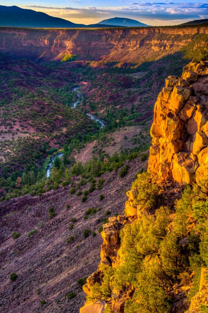 The cliffs and hills along the Rio Grande gorge in Wild Rivers Recreation Area are tinged orange and yellow by the setting sun.