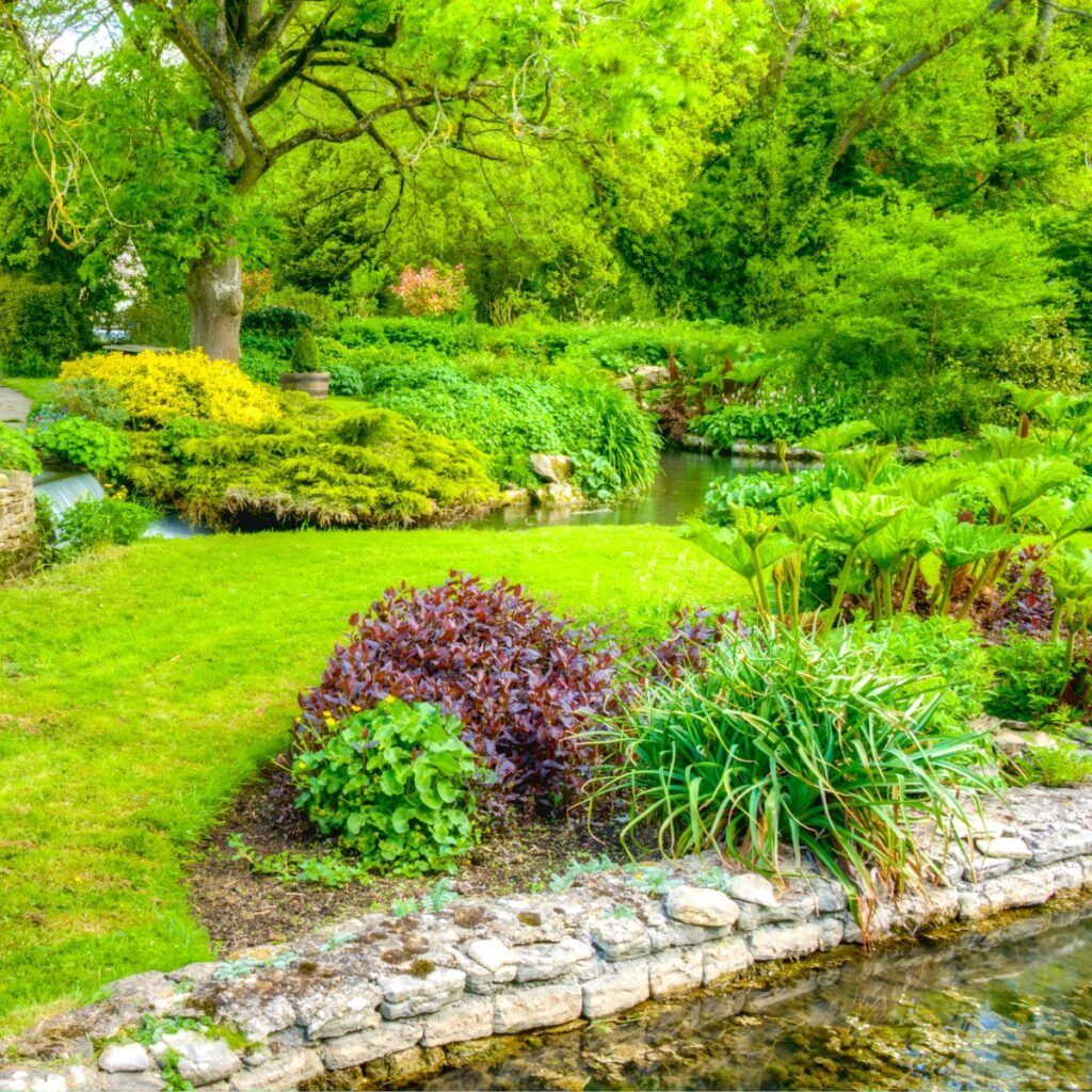 This is a typical May garden scene in Bibury along Bibury Spring, Gloucestershire, England.
