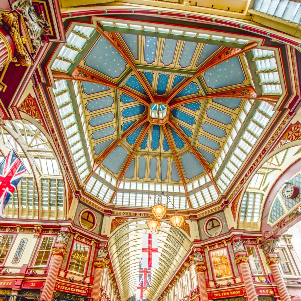 This is the ceiling of the main hall at Leadenhall Market in the City of London. The ornate roof structure, painted green, maroon and cream, and cobbled floors of the current structure were designed in 1881 by Sir Horace Jones.