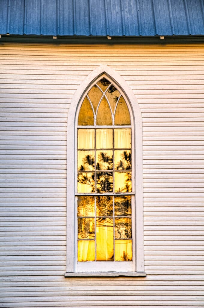 A pine tree is reflected in a window on the west side of the former St. Mary's Episcopal Church in Evergreen, Alabama.