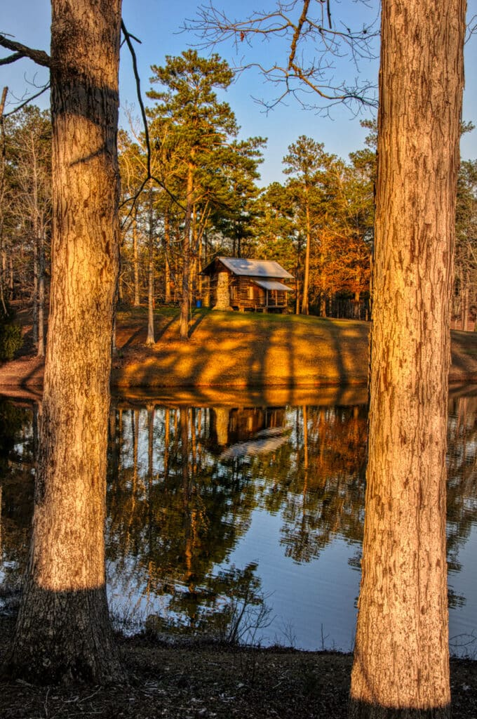 This restored cabin, framed by pine trees, sits near the lake in Evergreen Municipal Park in Evergreen, Alabama.
