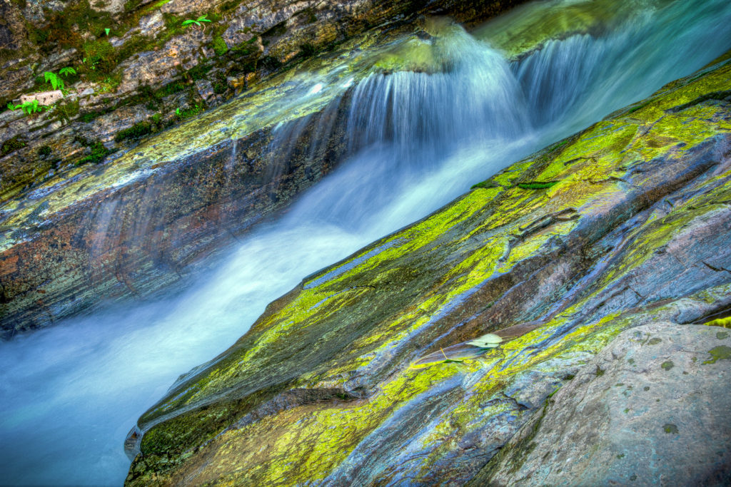 Water splashes along the cascade flowing through Sunrift Gorge in Glacier National Park, Montana.