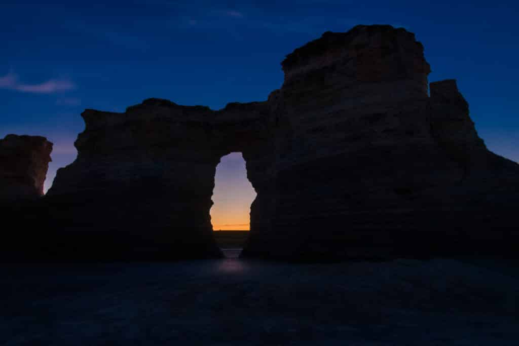 The first light of dawn is visible through a window in one of the formations at Monument Rocks near Oakley, KS.
