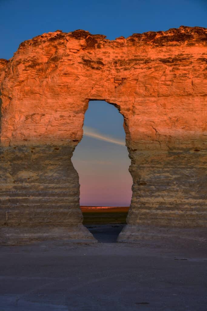 Cliffs of Niobrara Chalk glow orange as viewed through a window in one of the Monument Rocks formations near Oakley, KS.