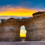 Sunrise colors shine through a window in one of the formations at Monument Rocks near Oakley, KS.