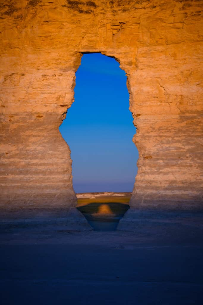 At sunrise, a shadow of a window appears through a window in one of the Monument Rocks formations near Oakley, KS.