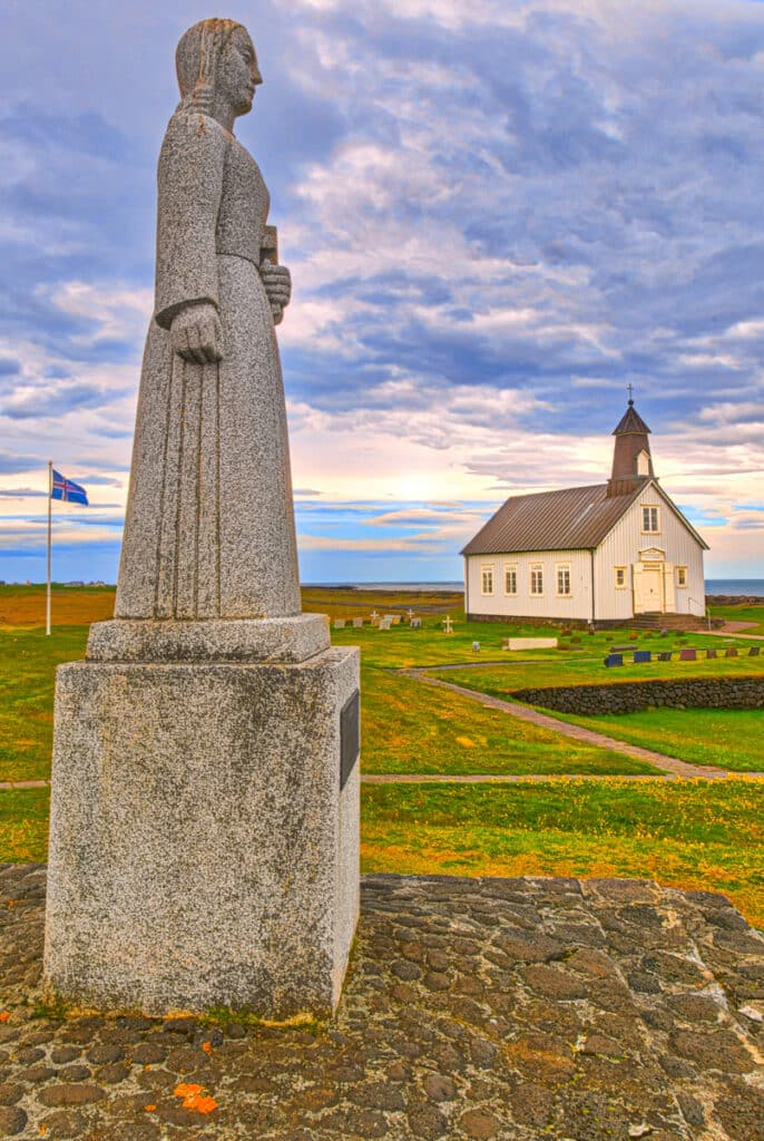 """This sculpture in Norwegian granite stands on the grounds of Strandarkirkja. Strandarkirkja loosely translates as """"coastal church."""" The name is fitting as the church overlooks the Atlantic and is visible from far at sea. It is locaded on the southern coast of the Reykjanes peninsula in Iceland."""
