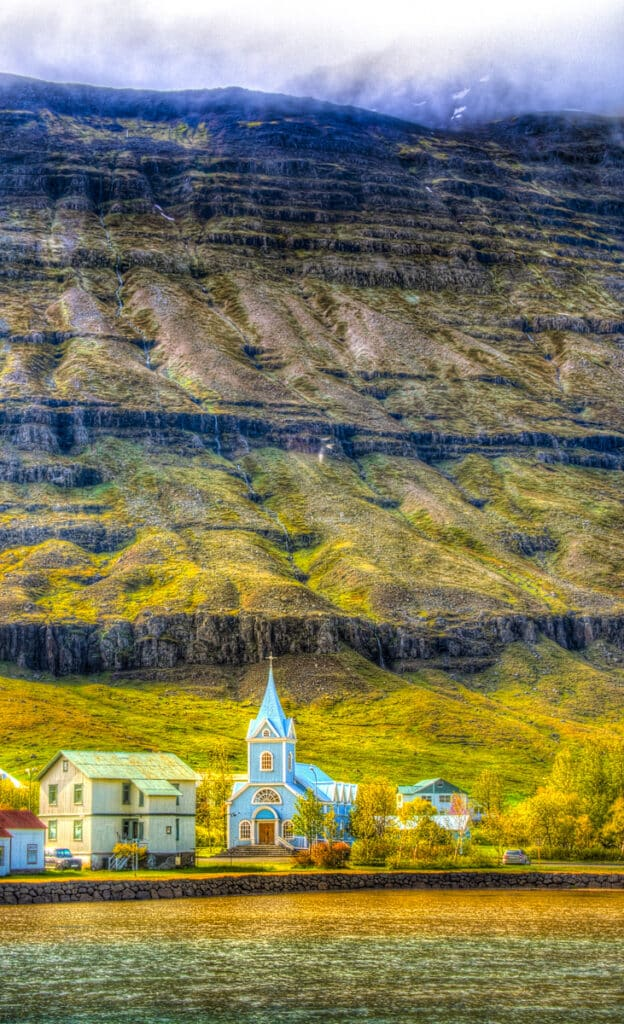This view of Bláa Kirkjan was taken from the opposite side of the fjord in the village of Seyðisfjörður.