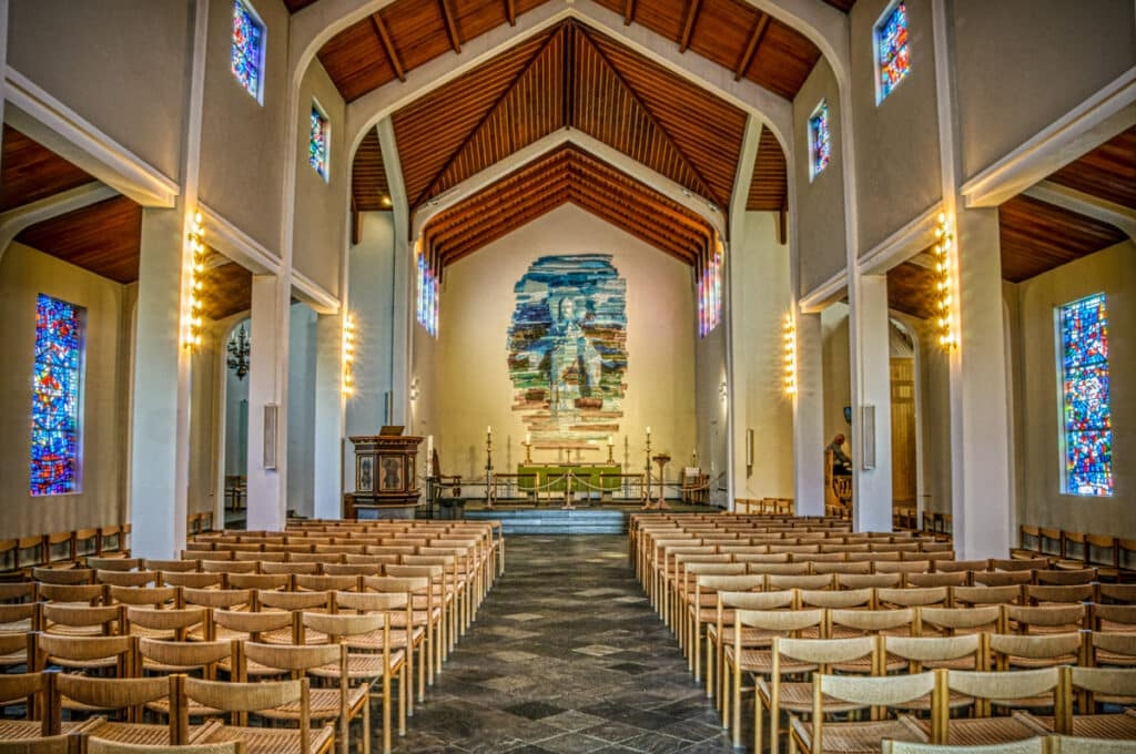 This is the interior view of Skálholt Church that features a vaulted ceiling, stained-glass windows, and mosaic altarpiece.
