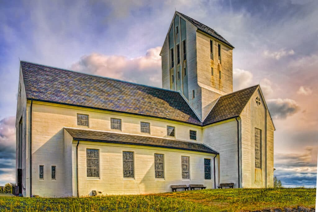 The community of Skálholt has been a center of religion in Iceland since 1056 AD. Today, it hosts a complex of libraries, offices, museums, historical ruins, graves, schools, and this church. Skálholt is located in southwestern Iceland.