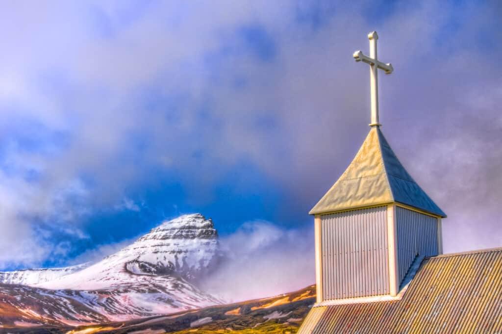 Peak of the mountain Dyrfjoll and the spire of the church Bakkagerðiskirkja in eastern Iceland.