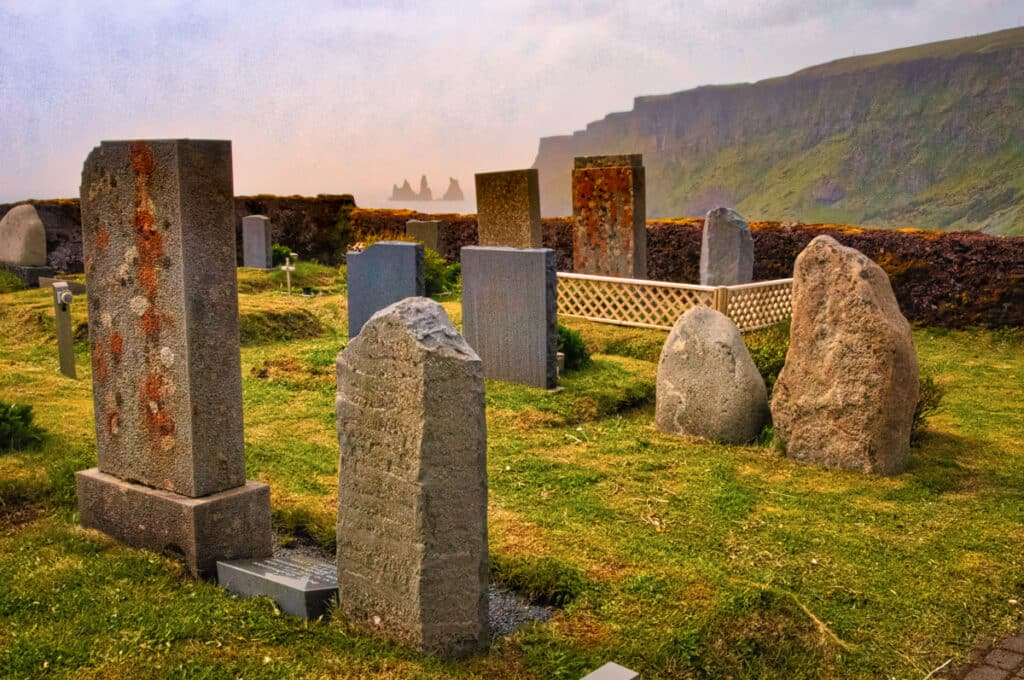 Tombstones in the cemetery at Vik in Iceland mimic the sea stacks of the Reynisdrangar spikes.