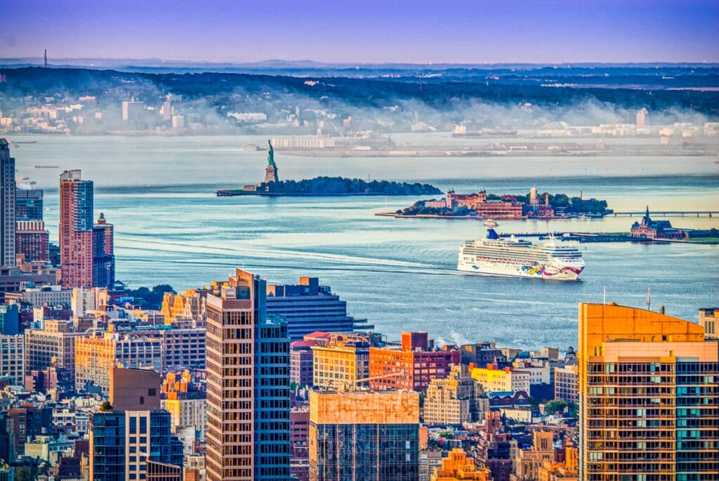 A sunrise view across the harbor to Ellis Island and the Statue of Liberty from 30 Rockefeller Center in New York City.