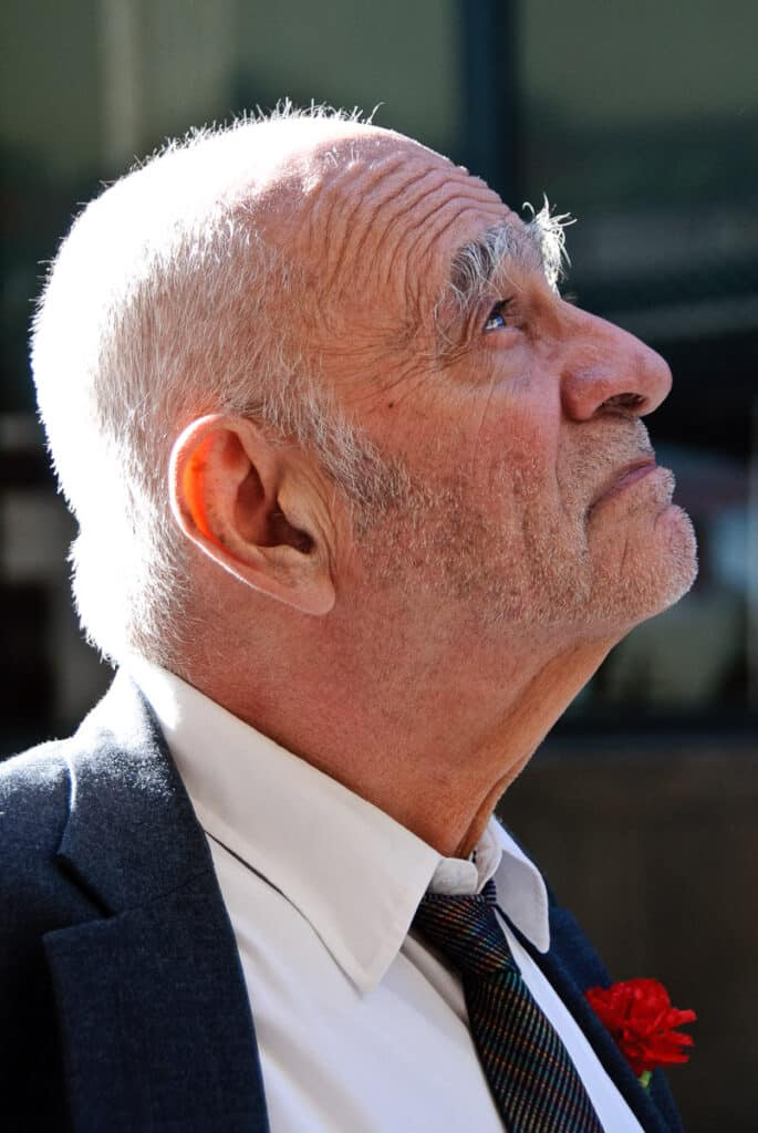 An old gentleman with a boutonniere looks up as he heads for coffee near Grand Central Station, New York City.