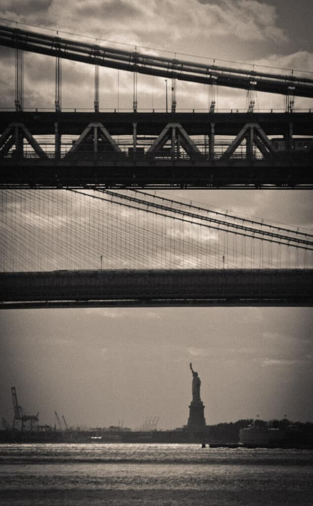 This foreshortened image shows the Statue of Liberty beyond the Brooklyn Bridge and the Manhattan Bridge in New York City.