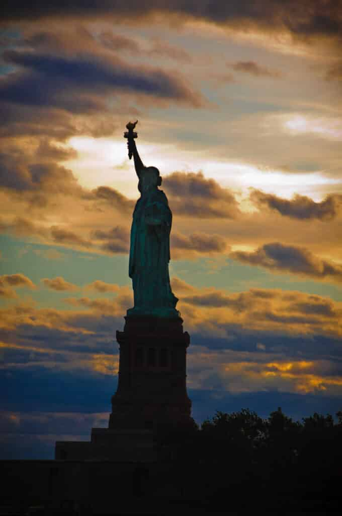 The Statue of Liberty is silhouetted against the evening sky in the Upper Bay of New York City.