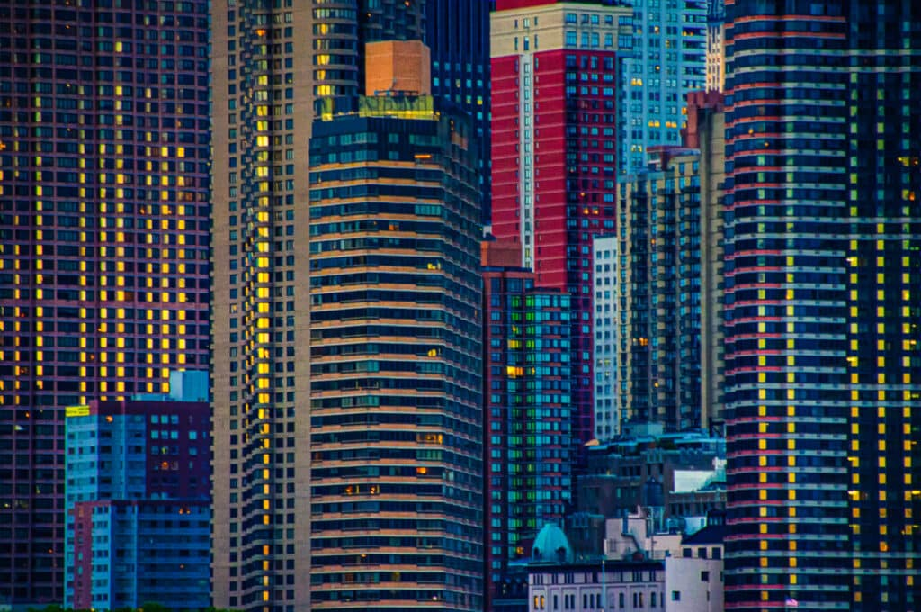Deep hues of blue, green, red, and gold glow as you travel through the canyons of Manhattan in New York City at night.