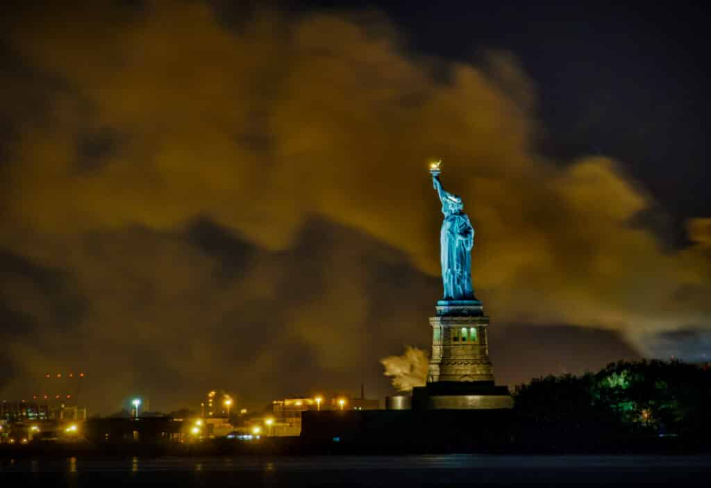 A view of the Statue of Liberty with smoke from a fire wafting from behind.