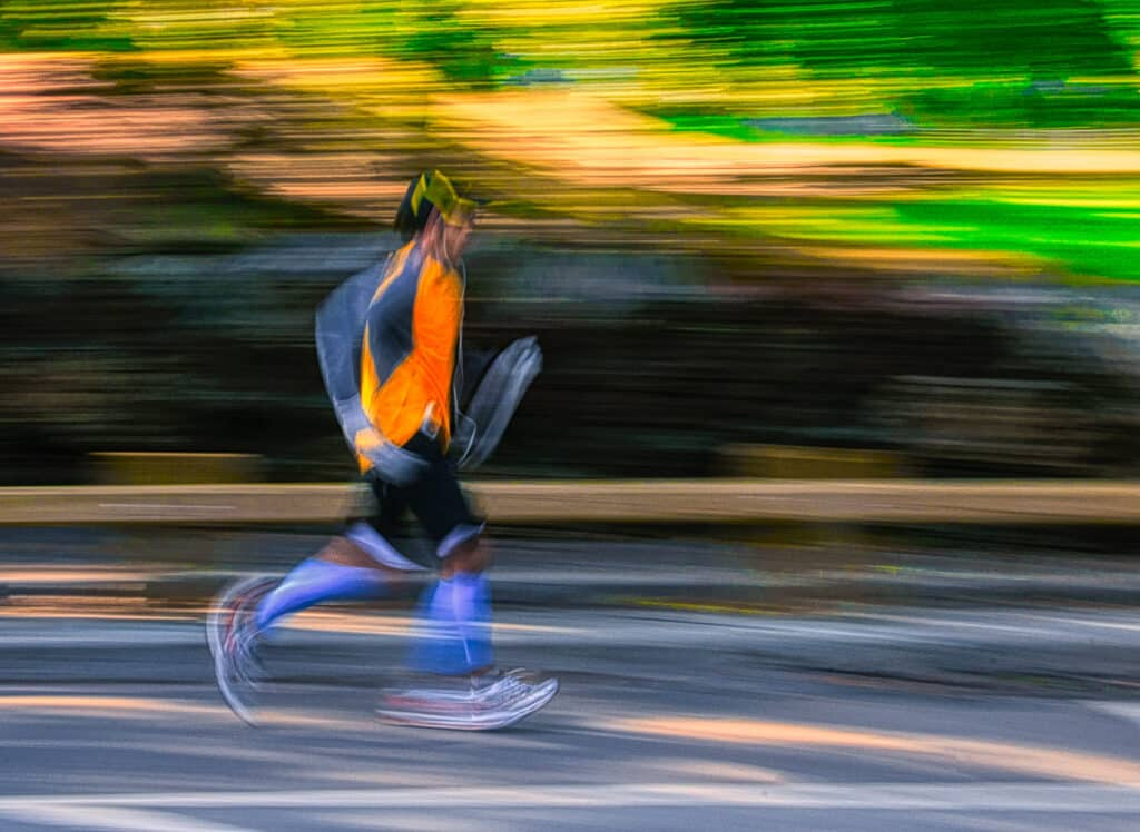 A panning shot creates and abstract image of a jogger running in Central Park, New York.
