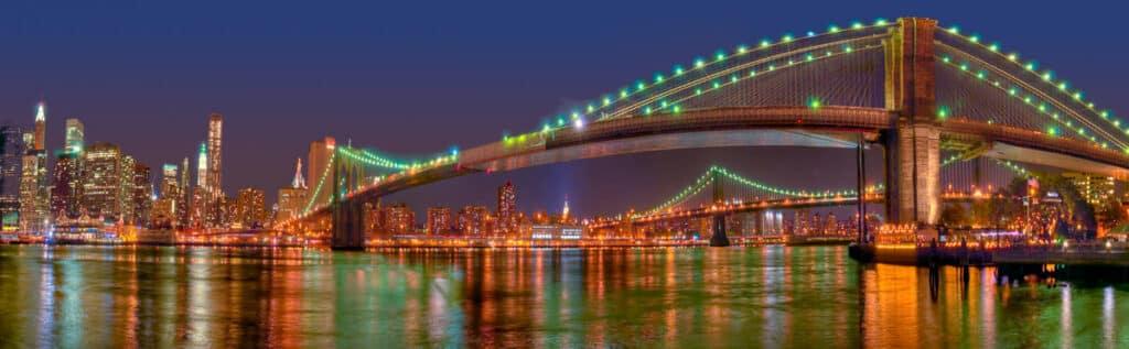 This nighttime panorama of the Brooklyn Bridge also features the Manhattan skyline and the Manhattan Bridge.