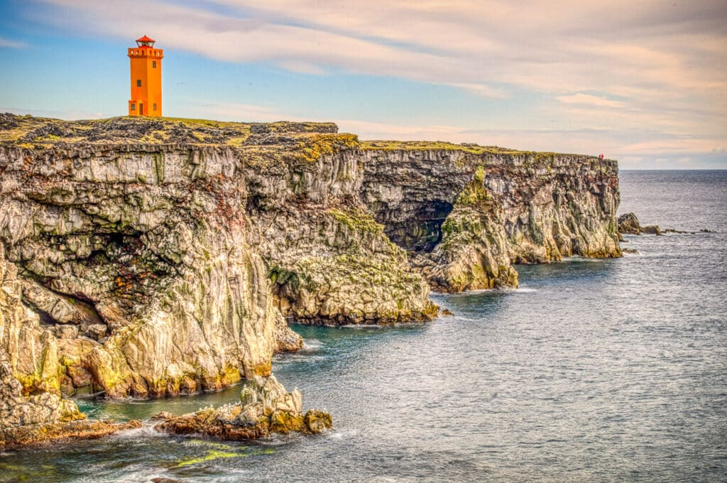 Lighthouse above the Svörtuloft cliffs at the western tip of the Snæfellsnes peninsula in Iceland.has two names. If you areon land, it is called Skálasnagaviti. If you are out at sea, it is called Svörtuloftaviti.