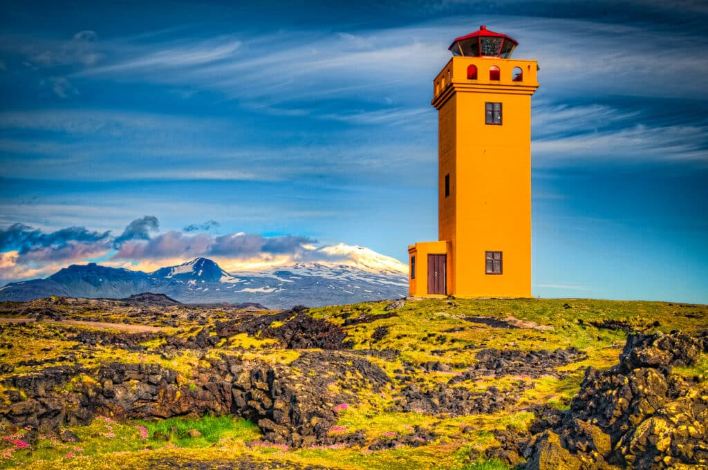 Lighthouse along the Svörtuloft cliffs at the western tip of the Snæfellsnes peninsula in Iceland. In the background is snowcapped peak of Snæfellsjökull National Park. If you are on land, it is called Skálasnagaviti. If you are out at sea, it is called Svörtuloftaviti.