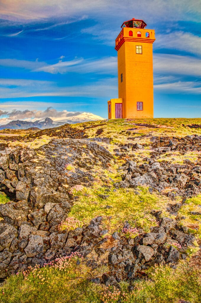 Lighthouse along the Svörtuloft cliffs at the western tip of the Snæfellsnes peninsula in Iceland. In the background is snowcapped peak of Snæfellsjökull National Park.