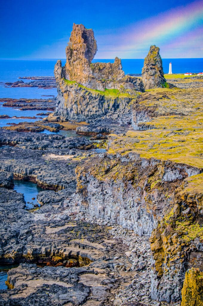 Rocky coast at Malarrif with the lighthouse in the distance, in Western Iceland.